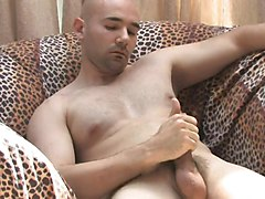 Sexy guy with a shaved head gets his cock stiff on a couch