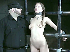 cute pale skin brunette is handcuffed to the metal bars
