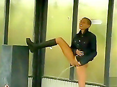 Shaved head girl pisses at a bus stop
